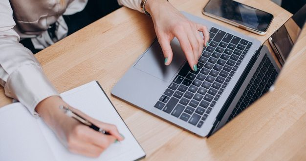 maos-femininas-escrevendo-no-bloco-de-notas-e-trabalhando-no-computador