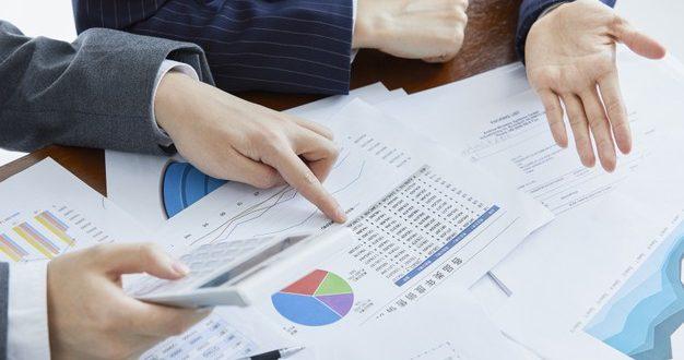 empresarios-em-ternos-elegantes-em-uma-reuniao-de-negocios-fazendo-calculos-no-escritorio